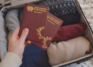 dois-passaportes-portugueses-erguido-sobre-uma-mala-de-viagem-com-roupa.-Foto-de-Cláudia-Paiva-886x590